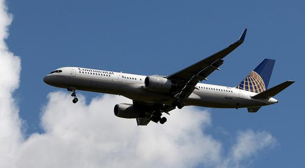A man faces jail he admitted trying to open the door of a Continental Airlines jet in mid-flight