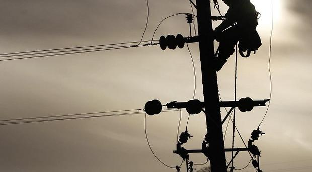 A linesman repairs an overhead line to restore electricity to Shieldhill, Scotland