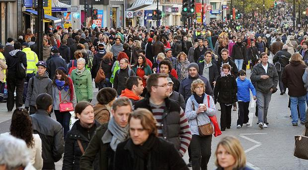 Christmas shoppers walk along the pedestrianised Oxford Street, London, which has been closed to traffic to attract shoppers