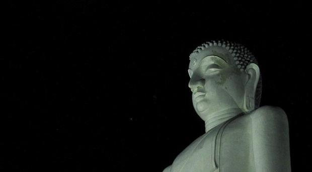 The lunar eclipse is seen in the sky beside a statue of Buddha in Kurunegala, Sri Lanka (AP)