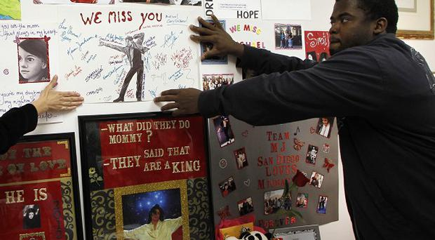 Michael Jackson fans hang a poster at a memorial where the headboard of the bed that Jackson was in on the day he died (AP)