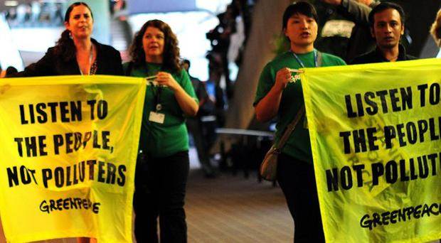 Greenpeace activists are escorted from the International Convention Centre in Durban, South Africa (AP)