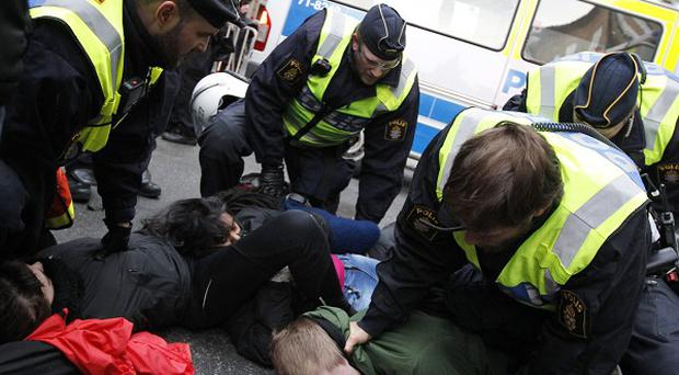 Anti-right wing demonstrators protesting against a right wing march are detained by Swedish police officers in Stockholm (AP/Scanpix)