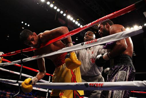 WASHINGTON, DC - DECEMBER 10: Amir Khan hangs over the ropes as Lamont Peterson is held back by referee Joe Cooper during their WBA Super Lightweight and IBF Junior Welterweight title fight at Washington Convention Center on December 10, 2011 in Washington, DC. (Photo by Al Bello/Getty Images)