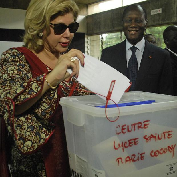 Ivory Coast President Alassane Ouattara looks on as his wife Dominique casts her vote in legislative elections (AP)