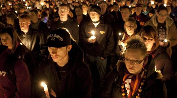 Members of the Virginia Tech community hold a candle light vigil to honour police officer Deriek Crouse who was shot dead (AP)