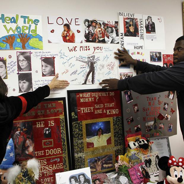 Michael Jackson fans hang a poster at a memorial (AP)