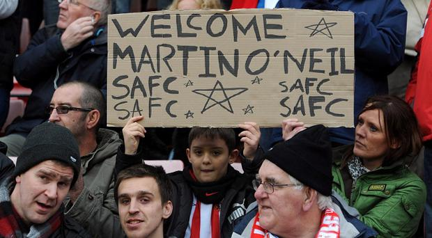 A young Sunderland fan welcomes their new manager Martin O'Neill in the stands with a sign during the Barclays Premier League match at the Stadium of Light, Sunderland