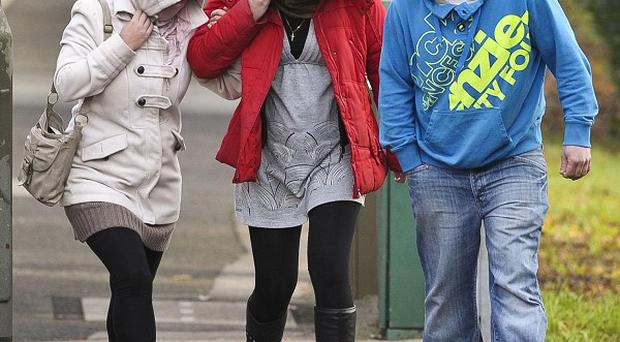 Gina Robins (centre) covers up as she walks up a street towards Torquay Magistrates' Court