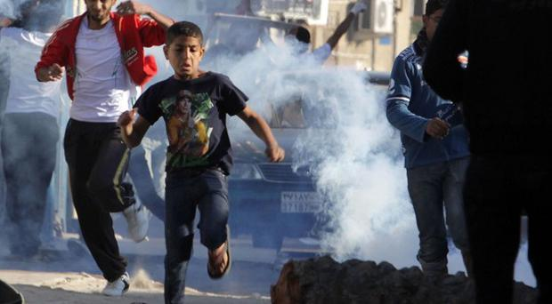 Anti-government protesters run from tear gas in the Shiite village of Diraz (AP)
