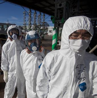 Workers enter the emergency operation centre at the Fukushima Dai-ichi nuclear power station in Okuma, Japan (AP)