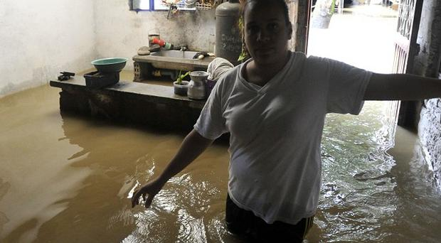 Jackeline Reyes, 24, walks through her flooded home in Juanchito in southern Colombia (AP)