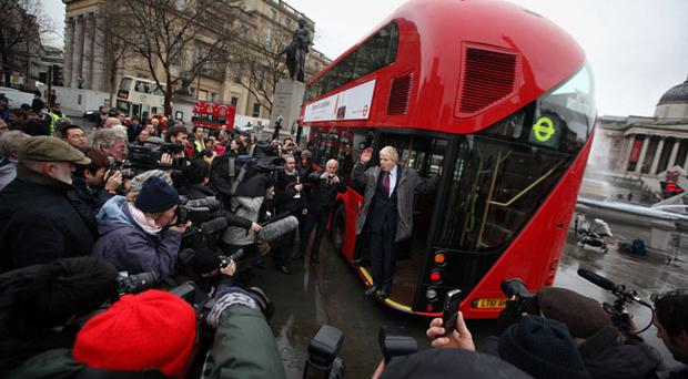 London Mayor Boris Johnson waves from a new prototype red double decker bus in Trafalgar Square on December 16, 2011 in London