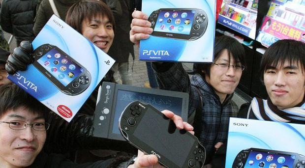 Some of the first people to buy the new PlayStation Vita show off their purchases (AP)
