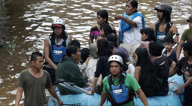 Volunteers use rubber a boat to ferry residents to safer grounds following a flash flood that inundated Cagayan de Oro city (AP)