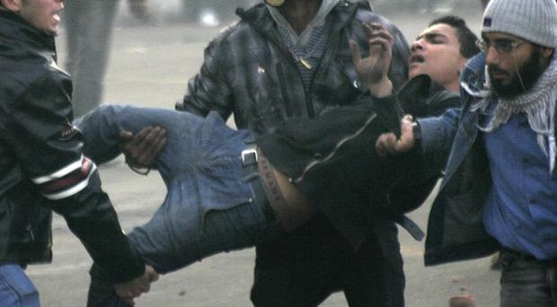 Egyptian protesters carry an injured fellow activist during clashes with military police near Tahrir Square in Cairo (AP)