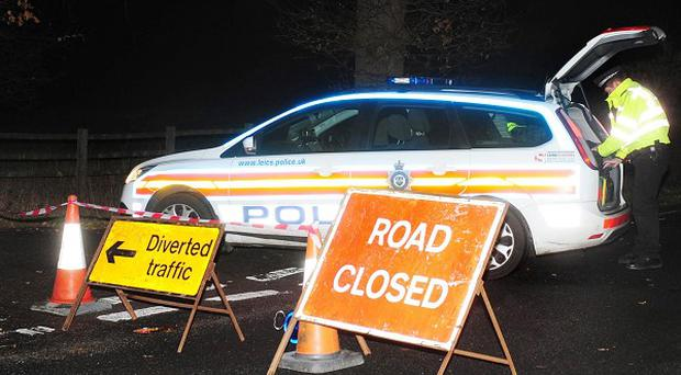 Police block the road near the scene in the Great Stretton area of Leicestershire after two light aircraft collided