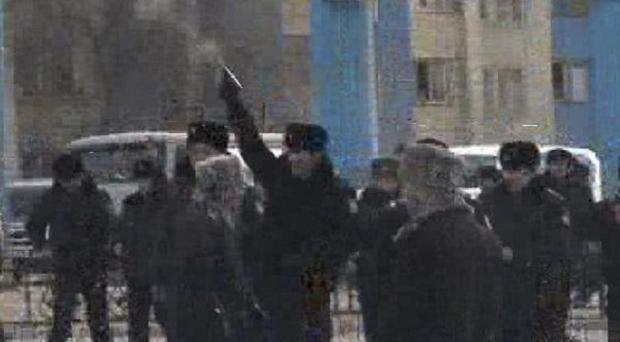 A Kazakh police officer fires a pistol to disperse demonstrators in the centre of Zhanaozen, Kazakhstan (AP/TV Station K-Plus)