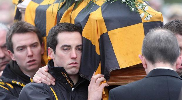 The coffin of murdered Crossmaglen Rangers player James Hughes is carried through Crossmaglen, Co Armagh, by his teammates