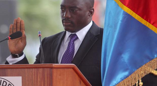 Incumbent Congo president Joseph Kabila holds the Congolese flag as he takes the oath of office as he is sworn in for another term (AP Photo)