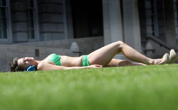 Sarah Docherty gets stripped off to soak up the sun in the grounds of Belfast City Hall. Summer 2011