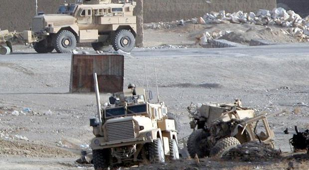 The wrecked armoured vehicle, right, which was carrying five Polish soldiers killed in an Afghanistan bomb attack (AP)