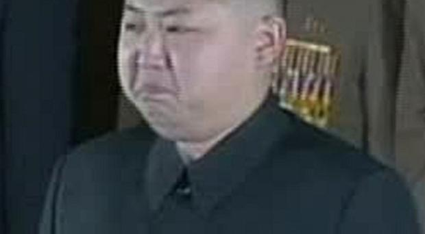 Kim Jong Un grimaces in front of the body of his father and North Korean leader Kim Jong Il at the Kumsusan Memorial Palace