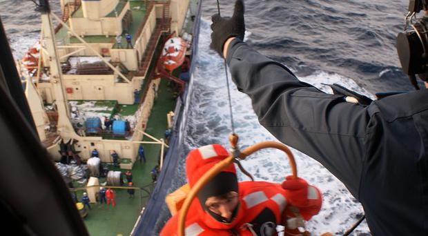 A survivor of the Kolskaya oil drilling platform is evacuated from a ship to a helicopter in the Sea of Okhotsk (AP)