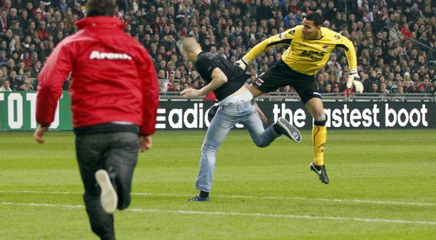 Keeper Esteban Alvarado, right, defends himself against an attacker who rushed from the stands as referee Bas Nijhuis, left, runs towards them during a cup match between Ajax and AZ Alkmaar in Amsterdam
