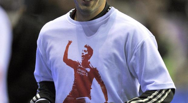 Liverpool's Luis Suarez wearing the T-shirt with his own image that the squad wore at Wednesday's Premier League clash at Wigan