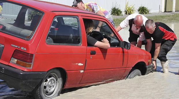 Residents help a driver to free his car from a sink hole near Christchurch (AP)