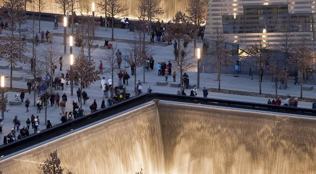 Visitors to the National September 11 Memorial walk around the twin pools in New York