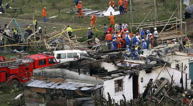 People and rescue workers gather at the site of a pipeline explosion in Dos Quebradas, Colombia (AP)