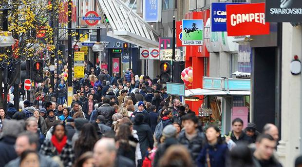 Christmas Eve shoppers on Oxford Street in central London as they collect their final gifts for Christmas