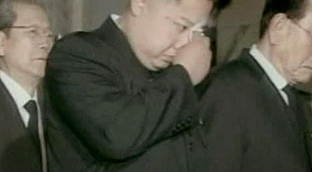 Kim Jong Un wipes his eyes with handkerchief as he views his father's body displayed in a glass coffin (AP Photo)
