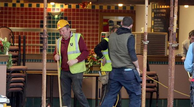 Workmen at the staff canteen at Quinn Group in Co Fermanagh, after a lorry was driven into the headquarters