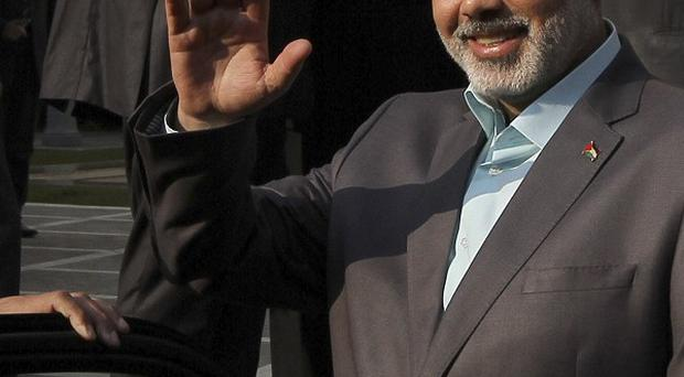 Gaza's Hamas Prime Ministe Ismail Haniyeh waves after meeting with Arab league Secretary General Nabil el-Arabi in Cairo (AP)