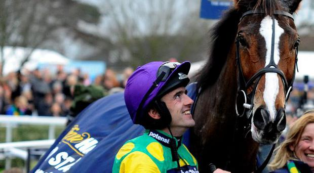 Ruby Walsh smiles as he looks at Kauto Star after winning The William Hill King George VI Steeple Chase at Kempton racecourse on December 26, 2011 in Sunbury, England.