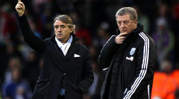West Bromwich Albion manager Roy Hodgson and Manchester City manager Roberto Mancini (left) on the touchline during the Barclays Premier League match at The Hawthorns, West Bromwich.