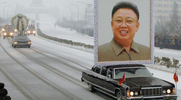 A portrait of late North Korean leader Kim Jong Il is carried past mourners during his funeral procession in Pyongyang (AP/Kyodo News)