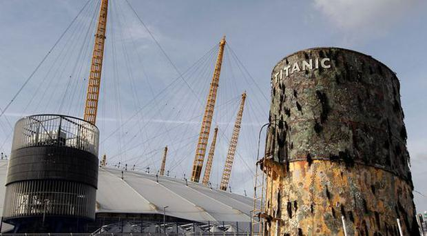 A replica of the upper section of the fourth funnel of the Titanic is towed along the river Thames past the O2 arena on 3 November 2010 in London. The replica funnel was created to launch a new exhibition of artefacts recovered from the wreck of the Titanic cruise liner.