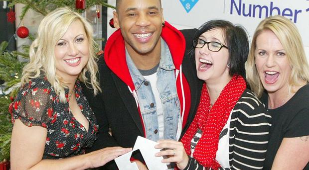 Military Wives Choir members Sam Stevenson, Nicky Kenyon and Kerry Riva get their Official Singles Chart Number 1 Award from Top of the Pops host Reggie Yates