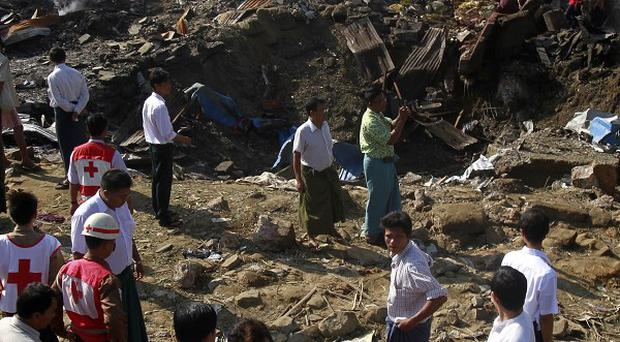 Rescue workers survey destroyed buildings and debris in Mingalar Taung Nyunt township in Yangon, Burma (AP)