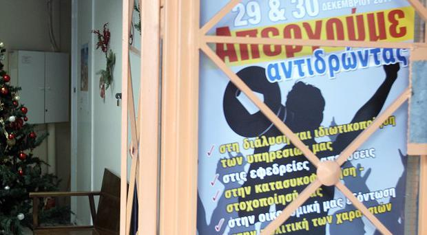 A poster reads: ''We strike in reaction...Dec.29 and 30, 2011'' at the entrance of a tax office in Greece (AP)