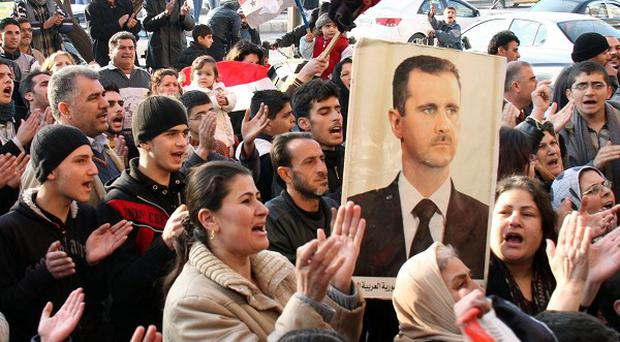 Pro-Syrian regime protesters chant slogans while one holds a picture of President Bashar Assad in the flashpoint city of Homs (AP)