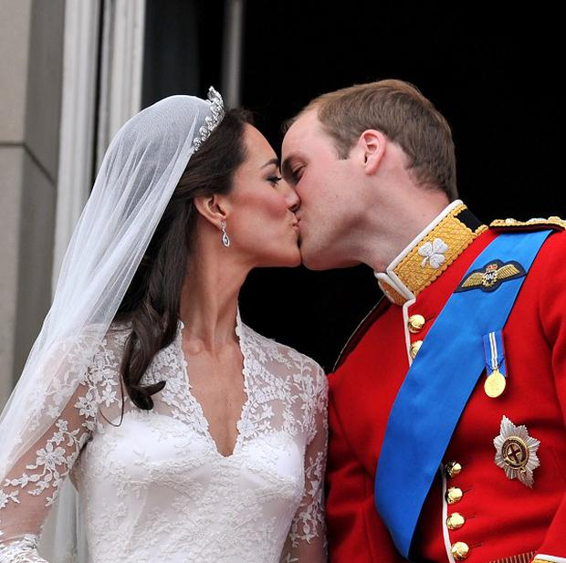 Prince William kisses wife Kate on the balcony of Buckingham Palace following their wedding at Westminster Abbey
