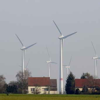 Wind turbines stand beside houses in the village of Feldheim, which is leading Germany's renewables revolution (AP)