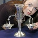 Frances Godden of Bonhams auction house inspects a silver table centrepiece from the a la carte restaurant on the White Star liner Titanic which sunk in 1912.