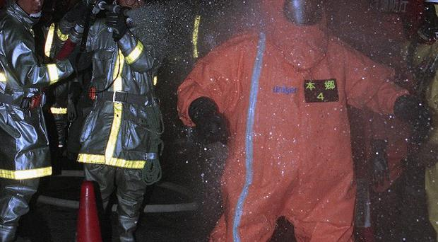 A chemical expert in a protection garment after investigating a sarin gas release in the Tokyo underground in 1995