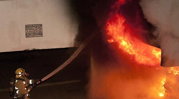A Los Angeles Fire Department firefighter extinguishes multiple cars on fire in a carport (AP)